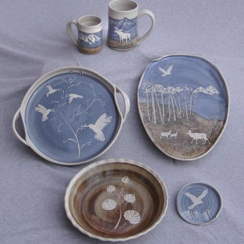 Examples of several forms with my slip work--painting pigmented clay around stencils and natural resists.